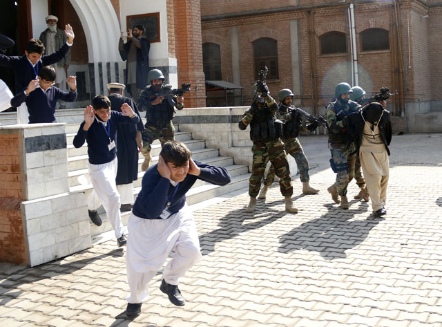 Schoolchildren flee as army soldiers conducting an exercise to repel militant attacks detain a mock-militant (R) at the Islamia Collegiate School in Peshawar, Pakistan February 02, 2016. PHOTO: REUTERS