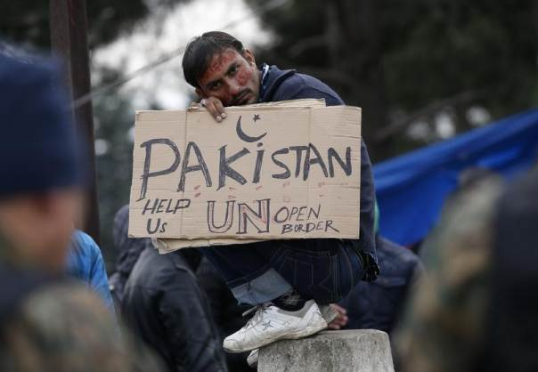 A migrant from Pakistan holds a placard while waiting to cross the border from Greece into Macedonia, near Gevgelija, Macedonia November 26, 2015. PHOTO: REUTERS