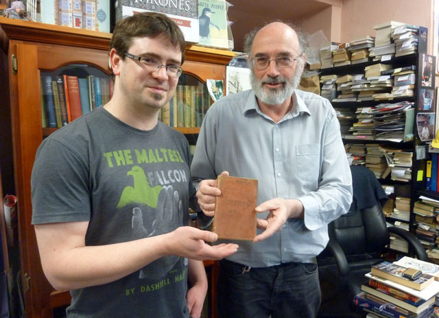 This handout photo taken and received on May 10, 2016 by Cracked and Spineless New and Used Books shows bookshop owners Richard Sprent (L) and Mike Gray (L) with the diary of British Lieutenant-Colonel John Squire, who served with the Duke of Wellington, which was discovered among a pile of books in a cupboard at the Cracked and Spineless New and Used Bookstore in the Tasmanian capital Hobart. PHOTO: AFP