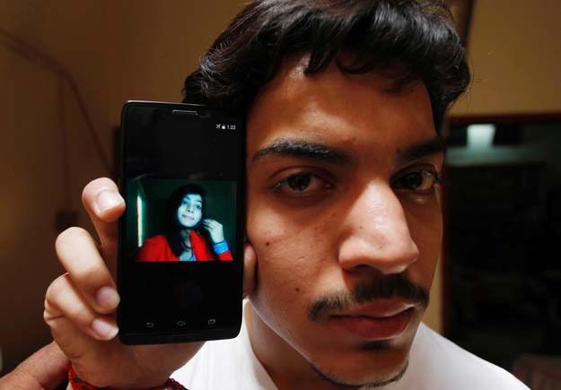 Hassan Khan shows the picture of his wife Zeenat Bibi, who was burnt alive by her mother, on his cellphone at his residence in Lahore on June 8, 2016. PHOTO: AFP