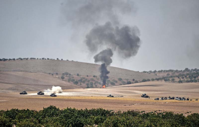 Turkish army tanks and pro-Ankara Syrian opposition fighter trucks positioned two kilometres west from the Syrian Turkish border town of Jarabulus. PHOTO: AFP
