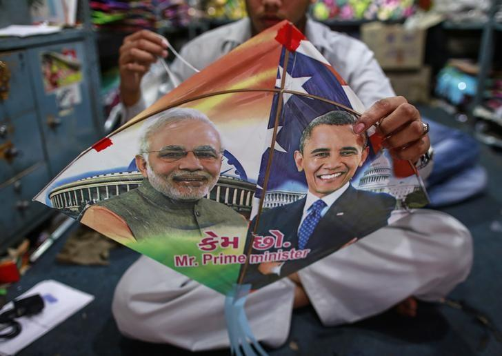 An employee ties threads on a kite, with portraits of Indian Prime Minister Narendra Modi (L) and US President Barack Obama, ahead of Obama's visit, in Mumbai. PHOTO: REUTERS