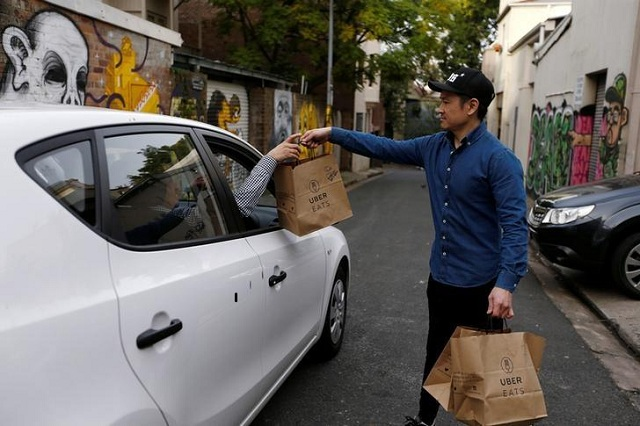 An Uber driver takes delivery of bags of donuts destined for a customer via Uber Eats in Sydney.PHOTO: REUTERS