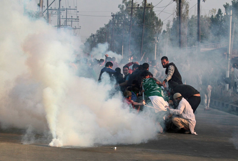 Kashmiri mourners hold the body of Junaid Ahmad, 12, as they are fired on with tear gas by Indian police during his funeral procession in downtown Srinagar on October 8, 2016. PHOTO: AFP