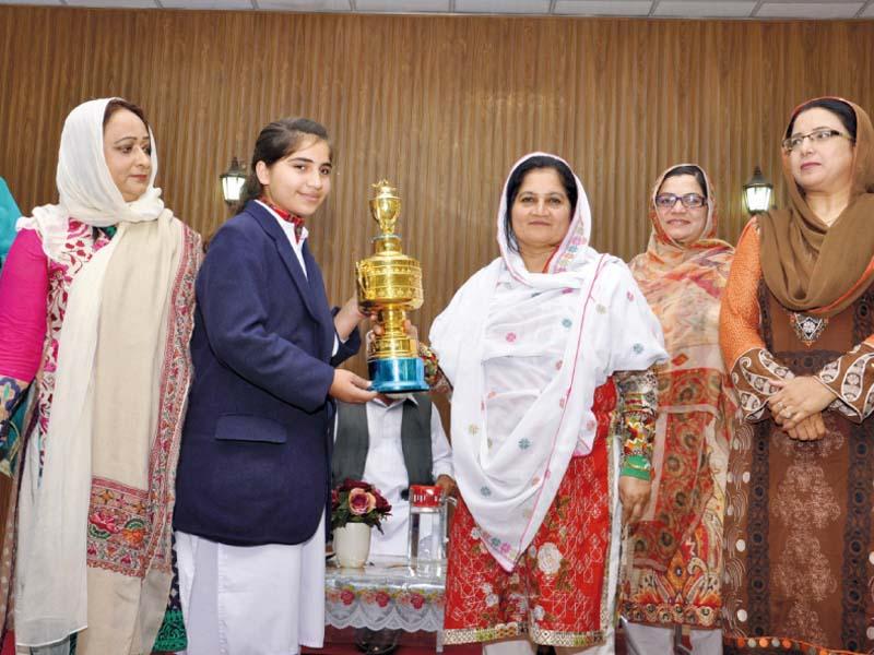 Abbottabad EDO Faiza Shafi presents a trophy to the declamation contest winner Bushra Azim. PHOTO: EXPRESS