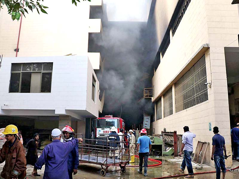 Firefighters seen busy putting out the fire that erupted on the ground floor of the textile mill. PHOTO: ONLINE