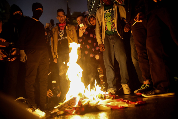 Protesters burn an American flag on Fifth Avenue outside of Trump Tower, November 9, 2016 in New York City. PHOTO: AFP