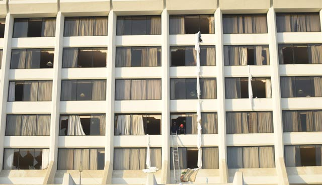 Fire fighters look from a room of Regent Plaza Hotel following a fire in the Pakistan's port city of Karachi on December 5, 2016. PHOTO: AFP
