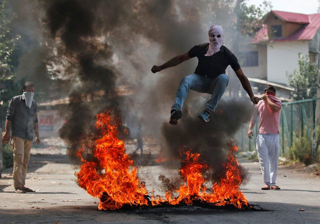 A man in a balaclava jumps over burning debris during a protest against the recent killings in Kashmir, in Srinagar, India September 12, 2016. PHOTO: REUTERS