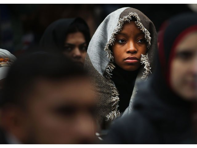 A woman listens to a speaker as area Muslims and local immigration activists participate in a prayer and rally against President Donald Trump's immigration policies on January 27, 2017 in New York City. PHOTO: AFP