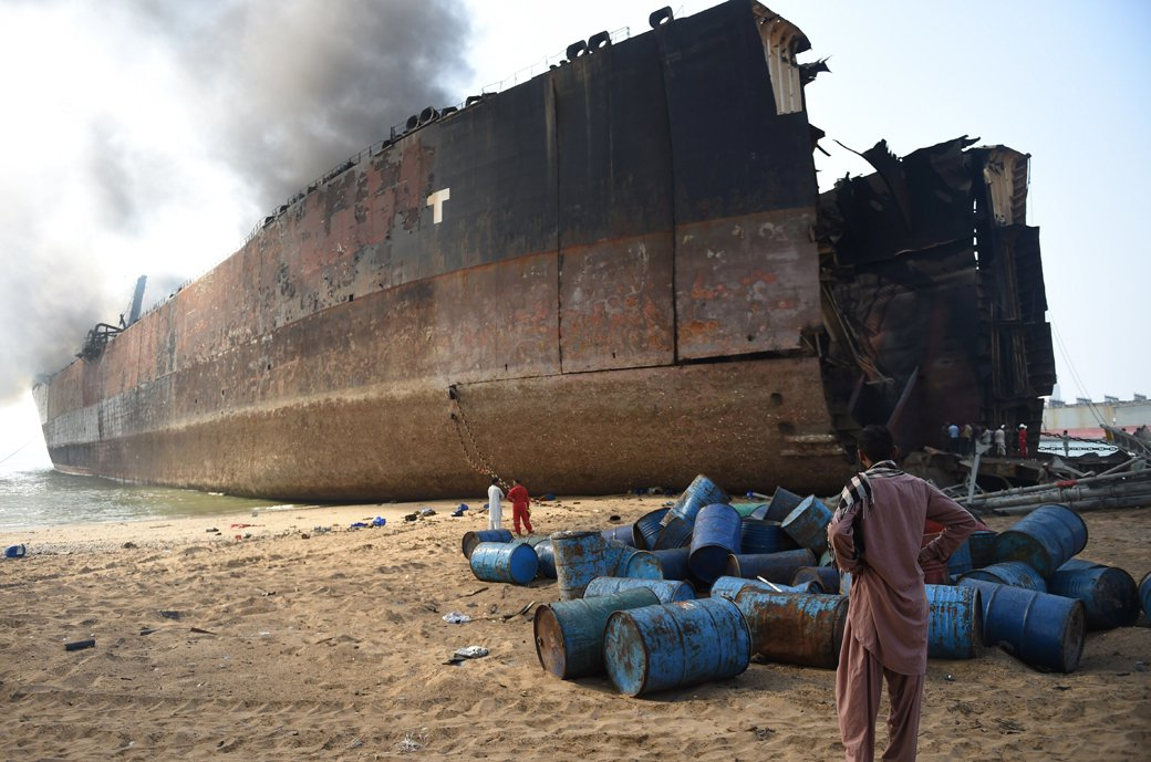 A man looks at the wreckage of a burning ship a day after a gas cylinder explosion at the Gadani shipbreaking yard on November 2, 2016. PHOTO: AFP