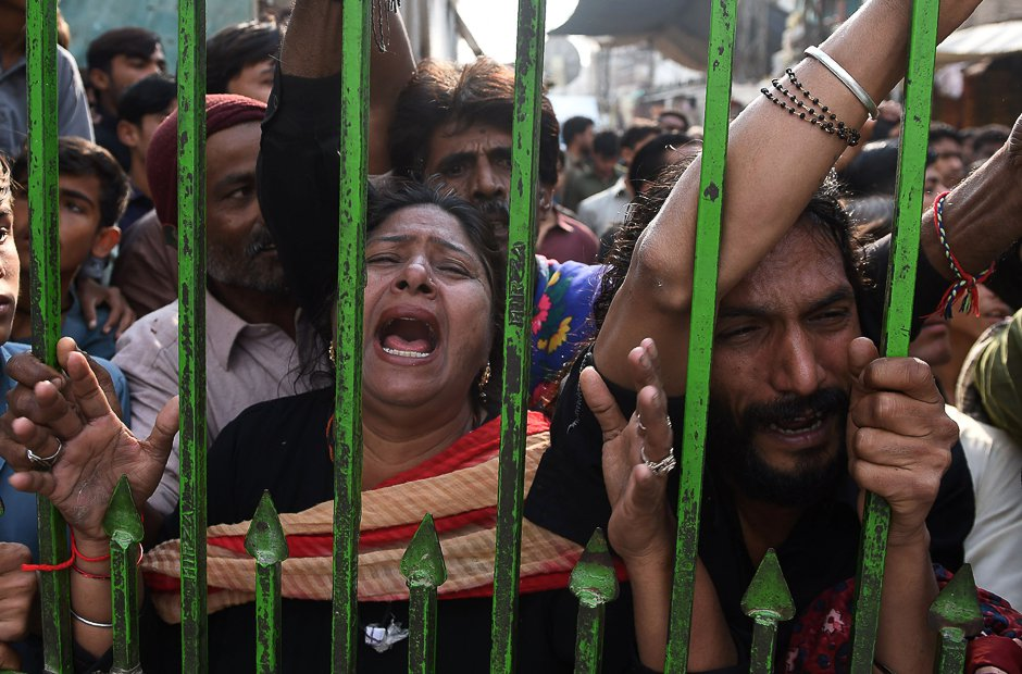 Devotees gather outside closed gate of Lal Shahbaz Qalandar shrine after a suicide attack killed over 80 people. PHOTO: AFP