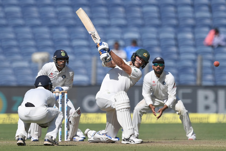 Australia's Mitchell Starc plays a shot as India's Ajinkya Rahane (L), Wriddhiman Saha (2L) and Murali Vijay (R) look on during the first day of the first Test cricket match between India and Australia at the Maharashtra Cricket Association stadium in Pune on February 23, 2017. PHOTO: AFP