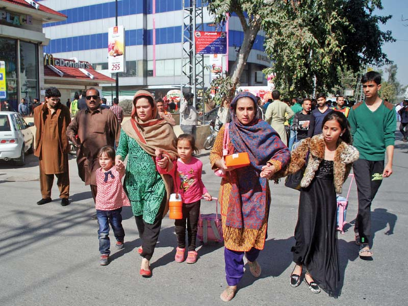 Families leave a market after hearing rumours of another blast in Gulberg on Thursday. PHOTO: ABID NAWAZ/EXPRESS