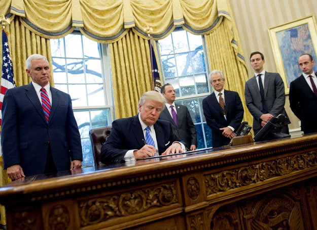 This file photo taken on January 23, 2017 shows US President Donald Trump signing an executive order alongside White House Chief of Staff Reince Priebus (C), US Vice President Mike Pence (L), National Trade Council Advisor Peter Navarro (3rd R), Senior Advisor Jared Kushner (2nd R) and Senior Policy Advisor Stephen Miller in the Oval Office of the White House in Washington, DC, January 23, 2017. PHOTO: AFP