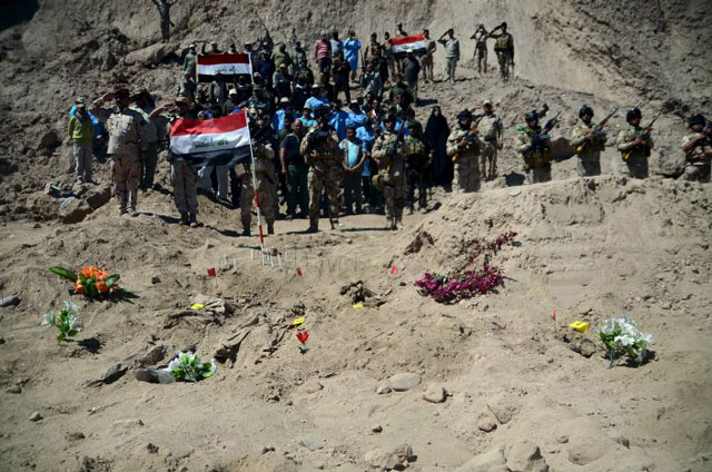 Iraqi soldiers salute as they stand next to a mass grave for Shia soldiers from Camp Speicher who have been killed by Islamic State militants in the presidential compound of the former Iraqi president Saddam Hussein in Tikrit April 6, 2015. PHOTO: REUTERS