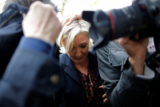 Marine Le Pen, French National Front (FN) party candidate for 2017 presidential election, is protected by bodyguards as eggs are thrown by demonstrators during her arrival in Dol-de-Bretagne, France, May 4, 2017. PHOTO: REUTERS