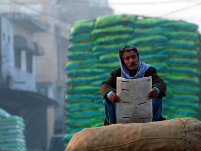 A man reads newspaper in the morning. PHOTO: REUTERS