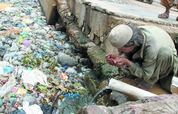 A man drinks water from a pipe installed in a sewage drain near Hyderabad Railway Station. The SC constituted the commission to probe the issue of non-provision of drinking water and sanitation in Sindh. PHOTO: ONLINE