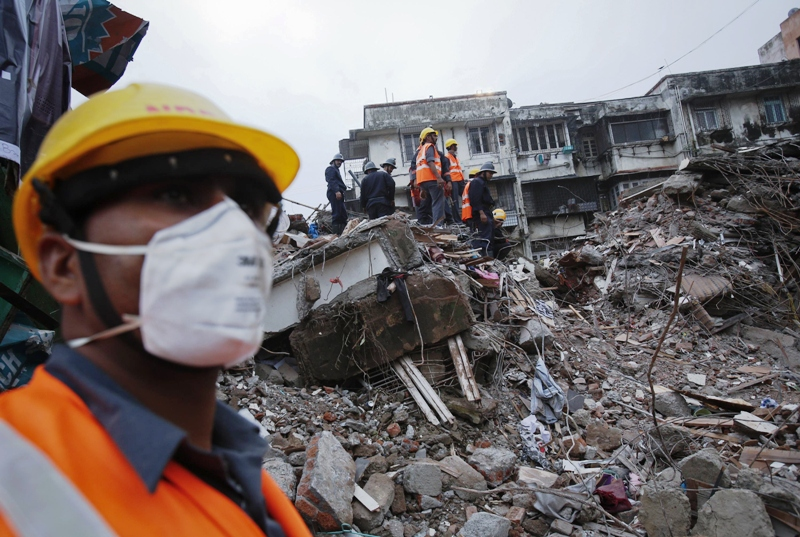 File photo: Rescue workers search through rubble at the site of a collapsed residential building in Mumbai early June 11, 2013.  PHOTO: REUTERS