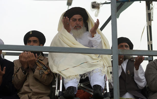 Head of the Tehreek-i-Labaik Yah Rasool Allah Pakistan (TLYRAP) Khadim Hussain Rizvi (C), offers Friday prayers on a blocked flyover bridge during a protest in Islamabad on November 24, 2017. PHOTO: AFP