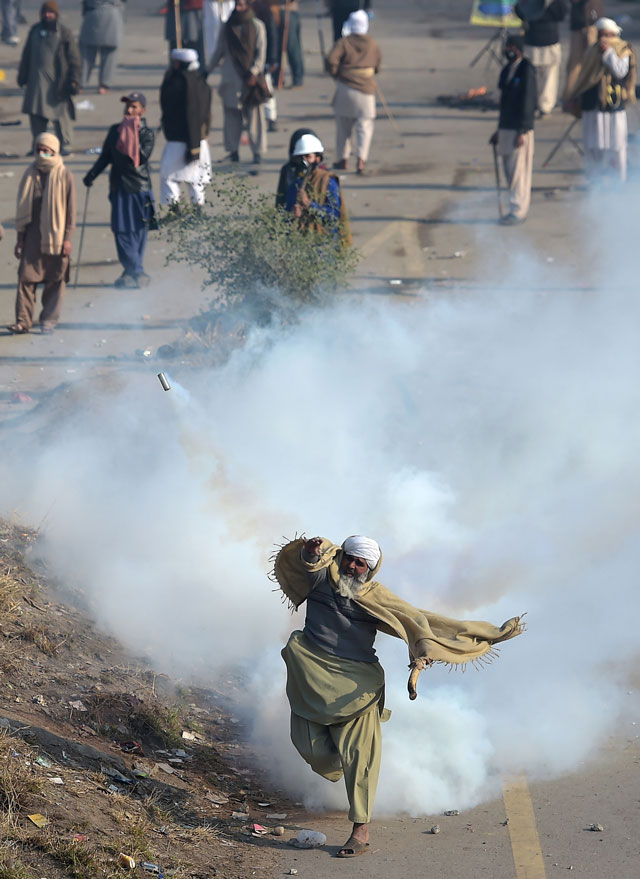 A protester of the Tehreeke Labaik throws a tear gas shell back towards police during a clash in Islamabad on November 25, 2017. PHOTO: AFP