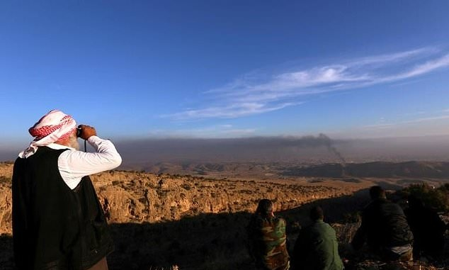 A Yazidi man watches on as Kurdish forces battle to end the Islamic State group's brutal rule over the Iraqi town of Sinjar. PHOTO: AFP