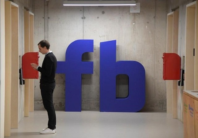 A man waits for an elevator in front of a logo at Facebook's headquarters in London, Britain, December 4, 2017.  PHOTO: REUTERS