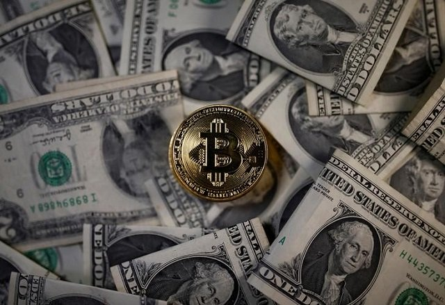 A bitcoin (virtual currency) coin placed on Dollar banknotes is seen in this illustration picture, November 6, 2017. PHOTO: REUTERS