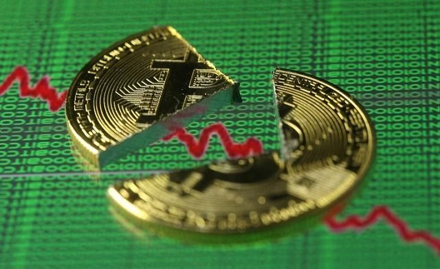 Broken representation of the Bitcoin virtual currency, placed on a monitor that displays stock graph and binary codes, are seen in this illustration picture, December 21, 2017. PHOTO: REUTERS
