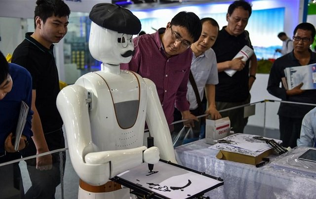 People watch a robot painting demonstration during the 19th China Hi-tech Fair in Shenzhen, south China's Guangdong Province, November 16, 2017. PHOTO: XINHUANET