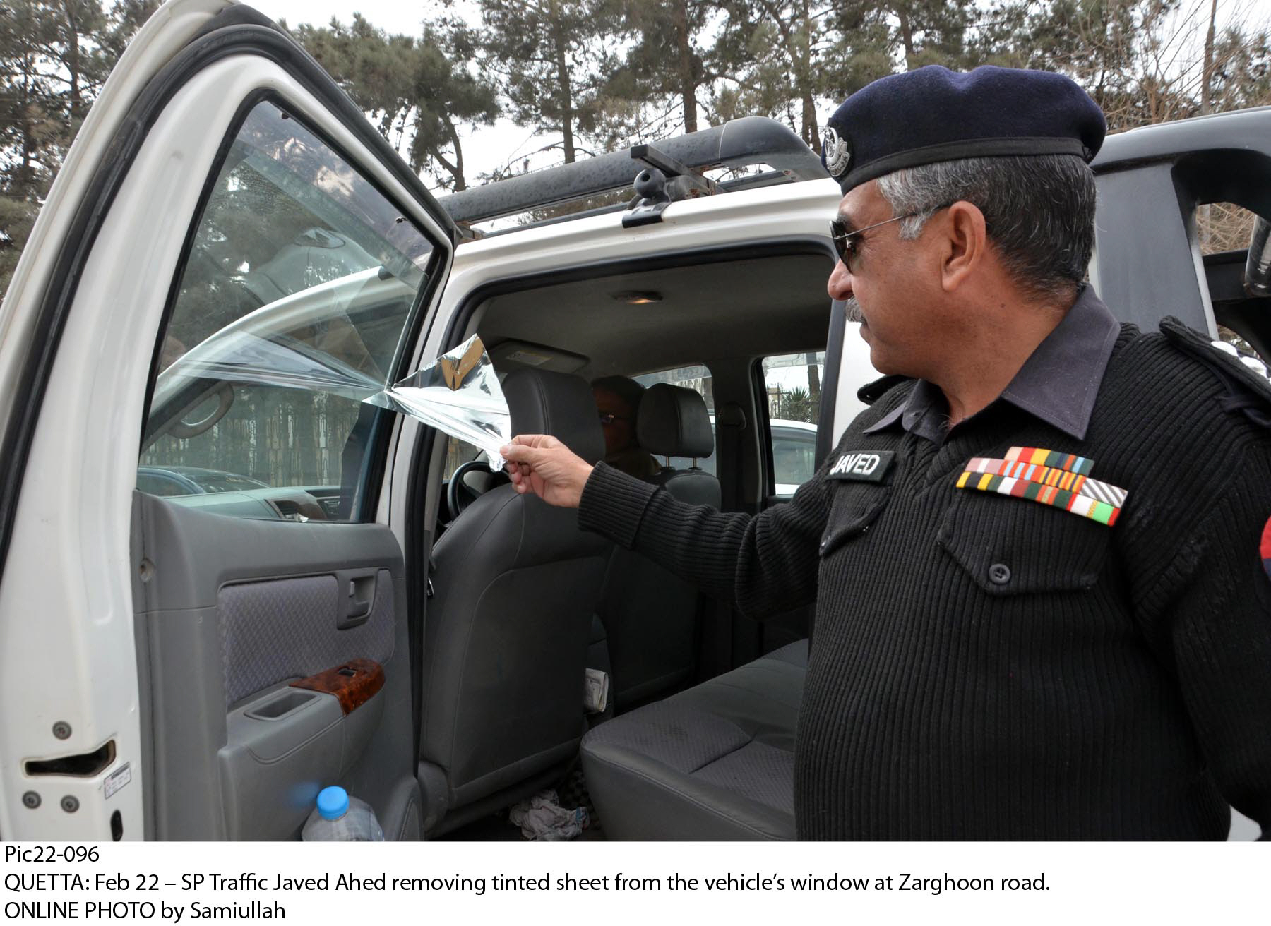 Traffic Superintendent of Police Javed Ahad removing tint from a vehicle's window on Zarghoon Road in Quetta. PHOTO: ONLINE