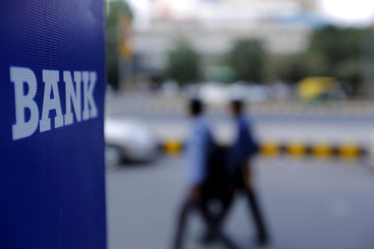 Commuters walk past a bank sign along a road. PHOTO: REUTERS