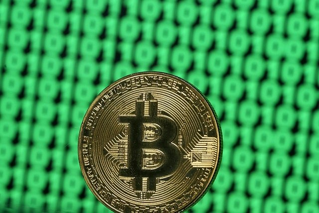 A token of the virtual currency Bitcoin is seen placed on a monitor that displays binary digits in this illustration picture, December 8, 2017. PHOTO: REUTERS