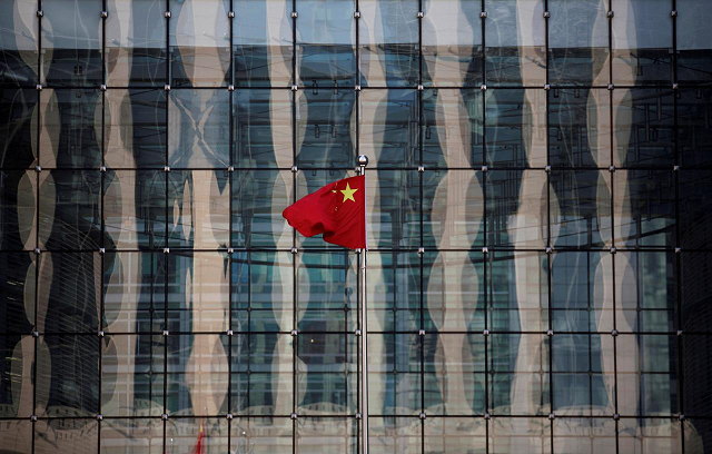 A Chinese national flag flutters at the headquarters of a commercial bank on a financial street in central Beijing, China November 24, 2014. PHOTO: REUTERS