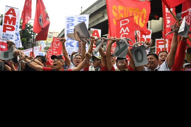 Activists along with workers break a mock chain during the May Day rally near Malacanang Palace PHOTO: AFP