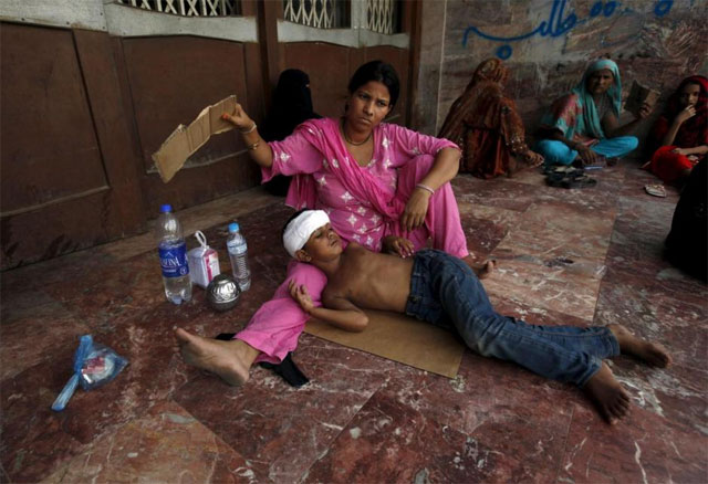 A woman uses a piece of cardboard to fan her son, while waiting for their turn for a medical checkup, outside JPMC during intense hot weather in Karach, June 23, 2015. PHOTO: REUTERS