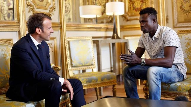 French president Emmanuel Macron (L) speaks with Mamoudou Gassama, 22, from Mali, at the presidential Elysee Palace in Paris, on 28 May 2018. PHOTO: AFP