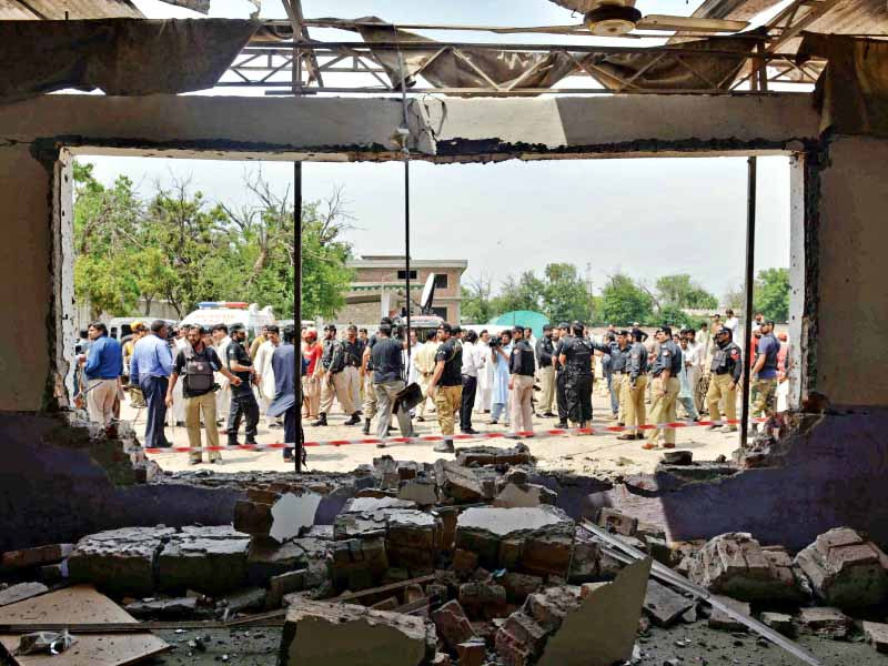Security officials gather at the site of the suicide bomb attack in Peshawar on Sunday. PHOTO: AFP