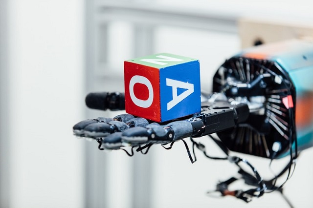 A lettered, multi-colored block rests on a human-like robotic hand in this undated handout photo. PHOTO: REUTERS