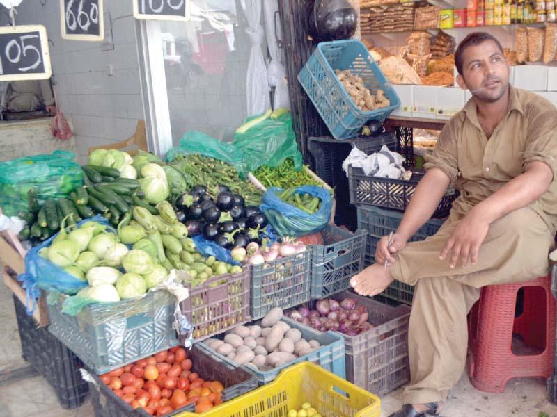 A vegetable vendor sits at his stall. PHOTO: WASEEM NAIZR/EXPRESS