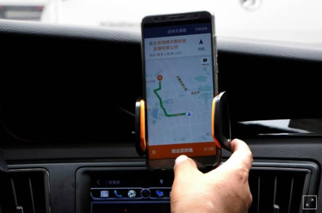 A Didi Chuxing driver checks the information on the application in his car in Beijing, China August 28, 2018. PHOTO: REUTERS