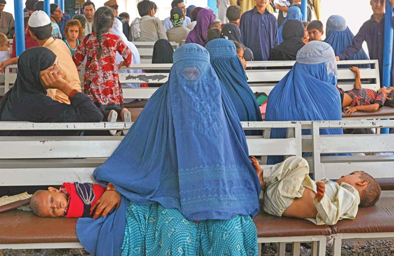 An Afghan refugee woman waits with her children to register at the UNHCR office. PHOTO: FILE