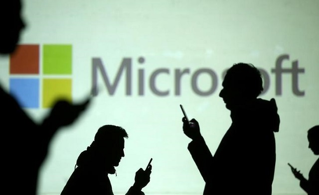 Silhouettes of mobile users are seen next to a screen projection of Microsoft logo in this picture illustration taken March 28, 2018. PHOTO: REUTERS