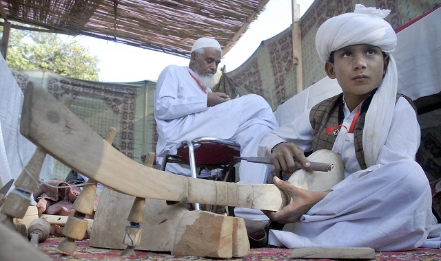 A young boy makes a traditional Baloch musical instrument during the 'Artisan at work' festival at Lok Virsa. PHOTO:ONLINE