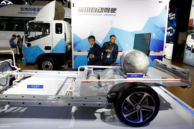 Visitors looks at the frame of an electric vehicle next to a Foton autonomous truck at the stall of the BAIC Group automobile maker at the IEEV New Energy Vehicles Exhibition in Beijing, China October 18, 2018. PHOTO: REUTERS