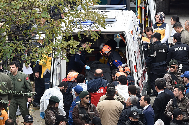 This handout picture released by Demiroren News Agency shows rescue workers and emergency services members  carrying a coffin of a soldier who died after a helicopter crash in Istanbul, on November 26, 2018. PHOTO: AFP