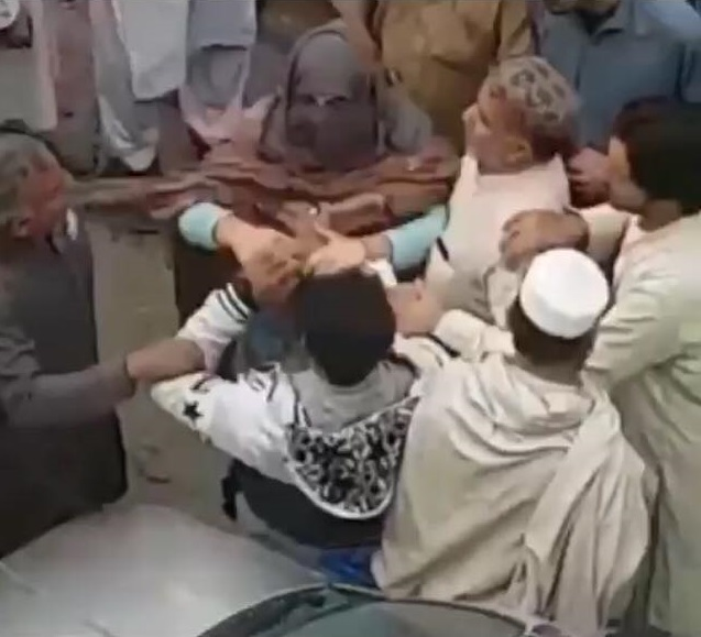 In the video footage, a woman can be seen furiously slapping and roughing up the two men. PHOTO: SCREEN GRAB