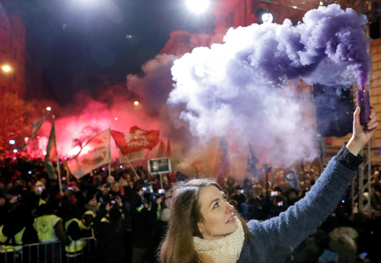 """Anna Donath, Vice President of the opposition party Momentum Movement, holds a flare during a protest against a proposed new labor law, billed as the """"slave law"""", in Budapest, Hungary. PHOTO: REUTERS"""