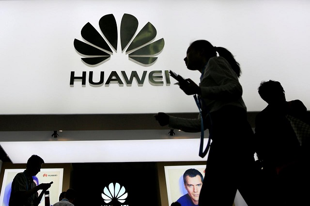 FILE PHOTO: People walk past a sign board of Huawei at CES (Consumer Electronics Show) Asia 2016 in Shanghai, China May 12, 2016. PHOTO: REUTERS